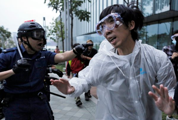 A protester is chased by a police officer outside government headquarters in Hong Kong