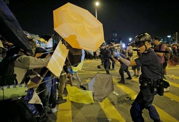 A police officer warns protesters to leave the main road outside government headquarters