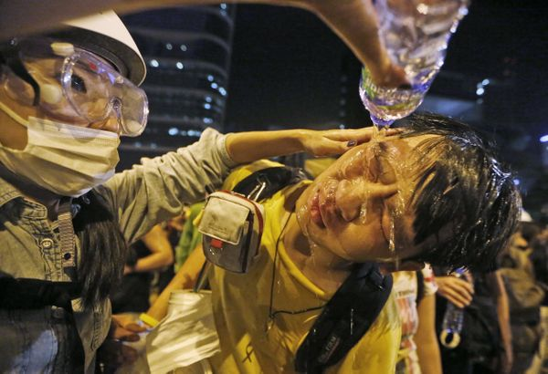 A pro-democracy protester washes his face after being hit by pepper spray outside government headquarters in Hong Kong
