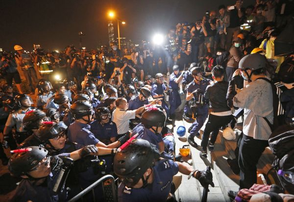 Pro-democracy protesters scuffle with police officers on the main road outside the government headquarters in Hong Kong