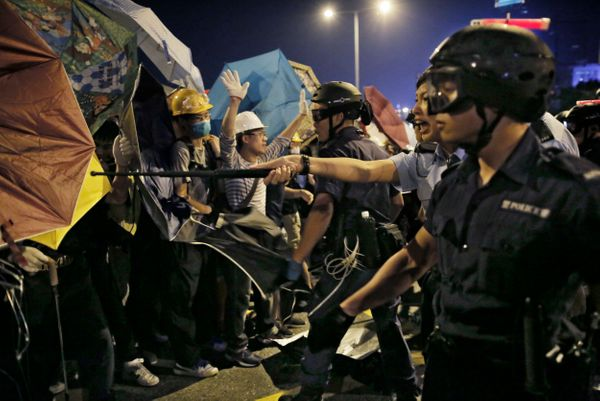 Police officers clash with protesters outside government headquarters in Hong Kong