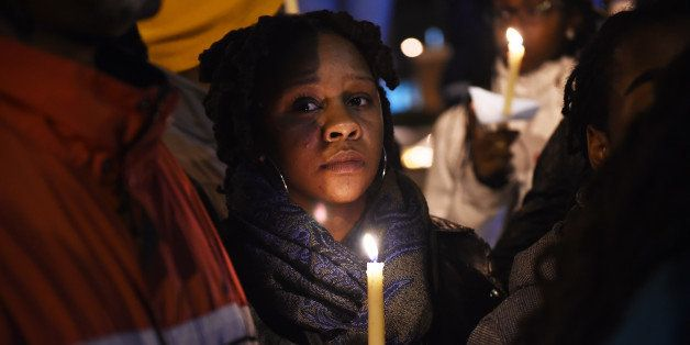 WASHINGTON, DC - NOVEMBER 23:  Dana Hall, center, holds a candle during a vigil along Martin Luther King Jr. Ave. SE as peopl
