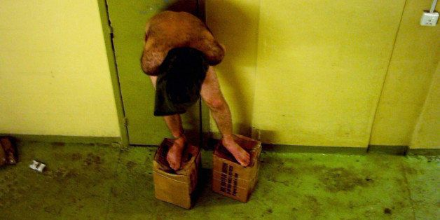 This is an image obtained by The Associated Press which shows a detainee standing on MRE boxes with a hood over his head in l