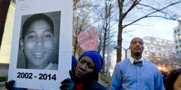 CORRECTS THE ID OF THE MALE ON POSTER TO TAMIR RICE - Tomiko Shine holds up a picture of Tamir Rice, the 12 year old boy fata