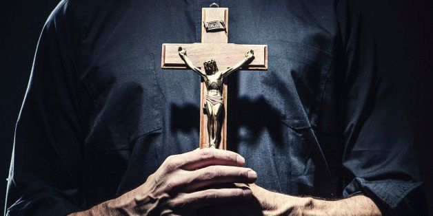 A dark high contrast image of a clergy man in a clerical collar holding a wooden portrayal of the crucifixion of Jesus Christ
