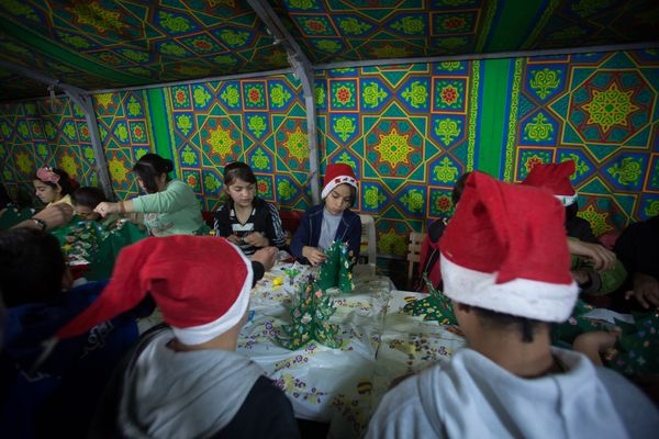 ERBIL, IRAQ - DECEMBER 12:  Iraqi Christian children make Christmas decorations in a school tent erected in the grounds of Ma