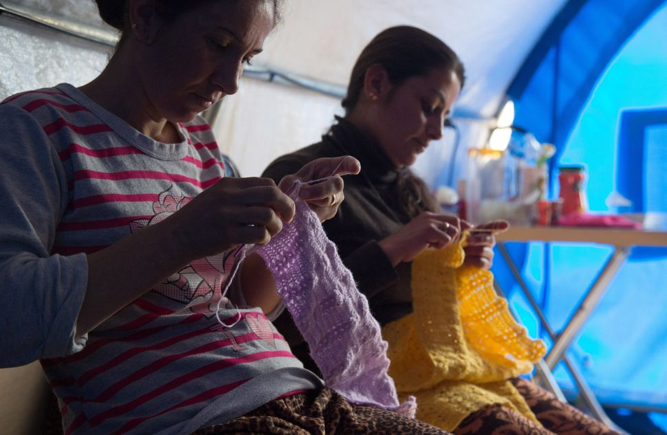 ERBIL, IRAQ - DECEMBER 07:  Iraqi Christian women knit jumpers for Christmas presents at a knitting club set up in a tent in