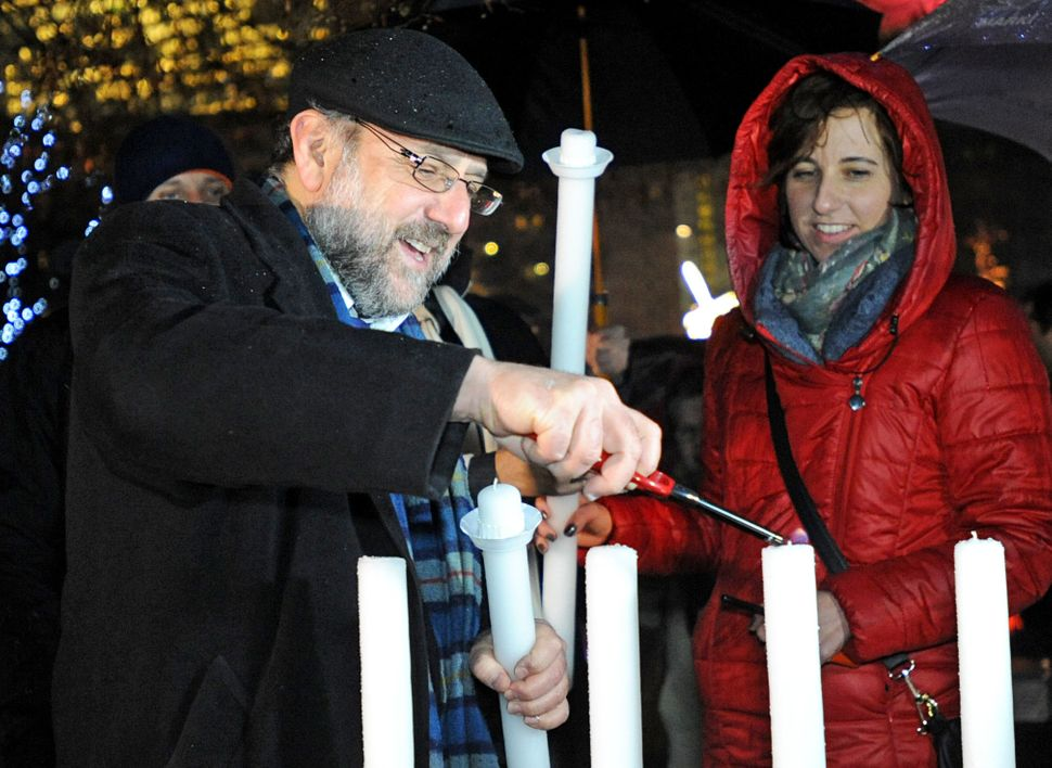 Poland's chief rabbi Michael Schudrich, left, lights the first candle celebrating the beginning of Hanukkah, the Jewish festi