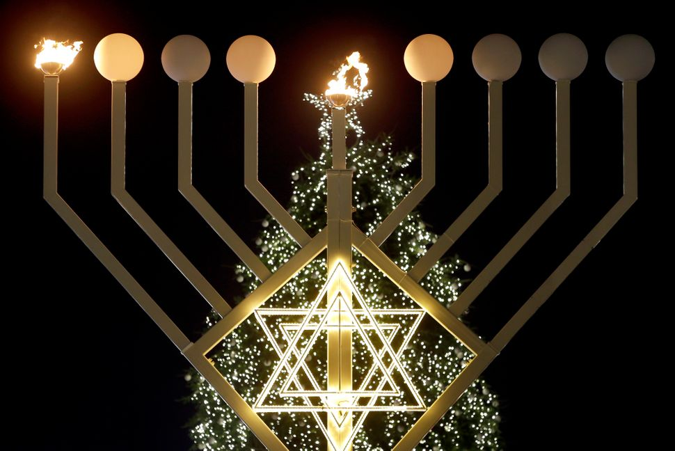 The first flames of a a giant Hanukkah Menorah in front of a Christmas tree at the Brandenburg Gate in Berlin, Germany, Tuesd