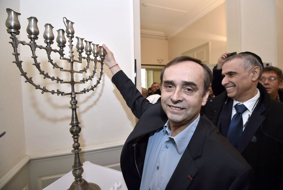 Mayor of the French city of Beziers Robert Ménard (L) lights the first of nine lights on the Hanukkah Menorah as president o
