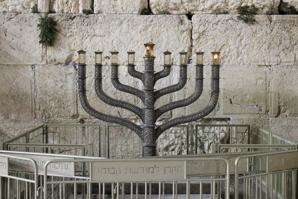 JERUSALEM - DECEMBER 16: The menorah of the Hanukkah, nine branched candelabrum is lighted in front of the Western Wall as th