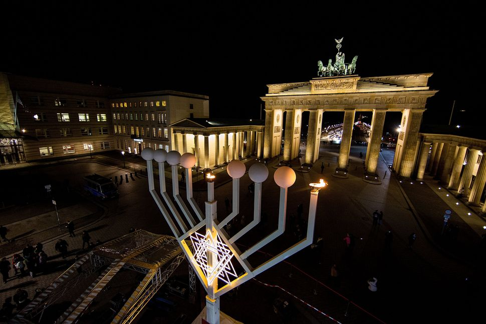 The first lamp of a large scale menorah  in front of the Brandenburg Gate lights after it was lights by Rabbis Yehuda Teichta