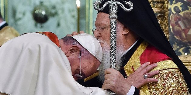 In this photo provided by Vatican newspaper L'Osservatore Romano, Ecumenical Patriarch Bartholomew I, right, kisses Pope Fran