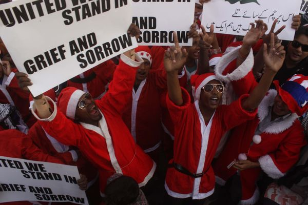 KARACHI, PAKISTAN - DECEMBER 21:  People wearing Santa Claus costumes shout slogans and hold banners as they stage a demonstr