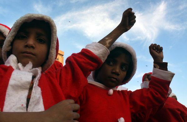KARACHI, PAKISTAN - DECEMBER 21:  Children wearing Santa Claus costumes react as they stage a demonstration in Karachi, Pakis