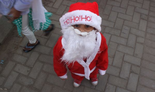 KARACHI, PAKISTAN - DECEMBER 21:  Child wearing Santa Claus costume attends a demonstration in Karachi, Pakistan, on December