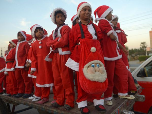 Pakistani minority Christian children dressed as Santa Claus pose during a Christmas peace rally in solidarity of the victims