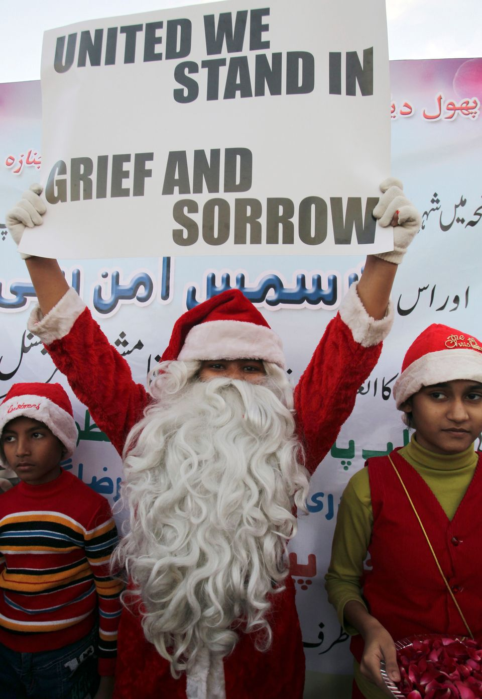 A Pakistani Christian boy dressed as Santa Claus holds a poster to condemn Tuesday's Taliban attack on a military-run school