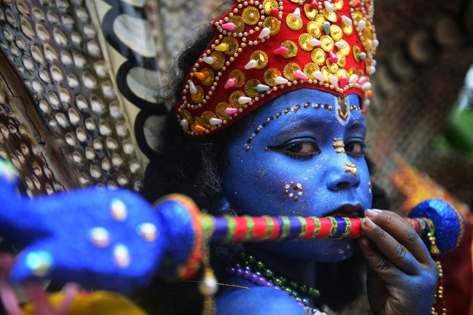 A Bangladeshi youth dressed as the Hindu god Lord Krishna takes part in a procession during celebrations for the Janmashtami