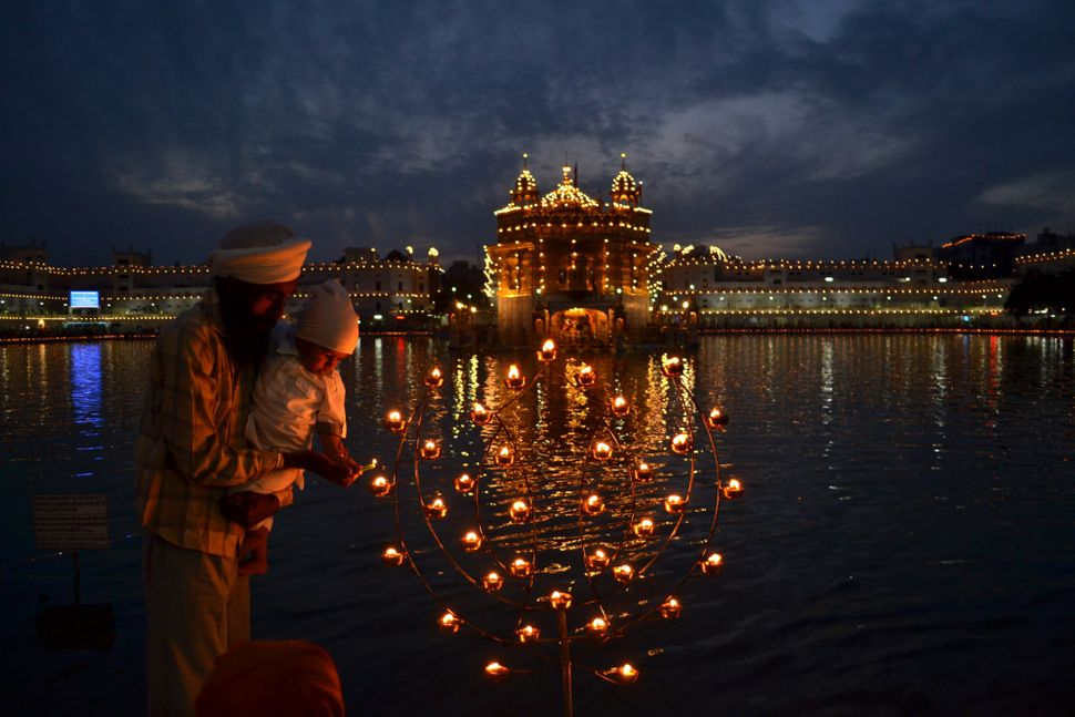 A Sikh father helps his son to light a lamp, near the illuminated Golden Temple, the Sikhs holiest shrine, on the festival of