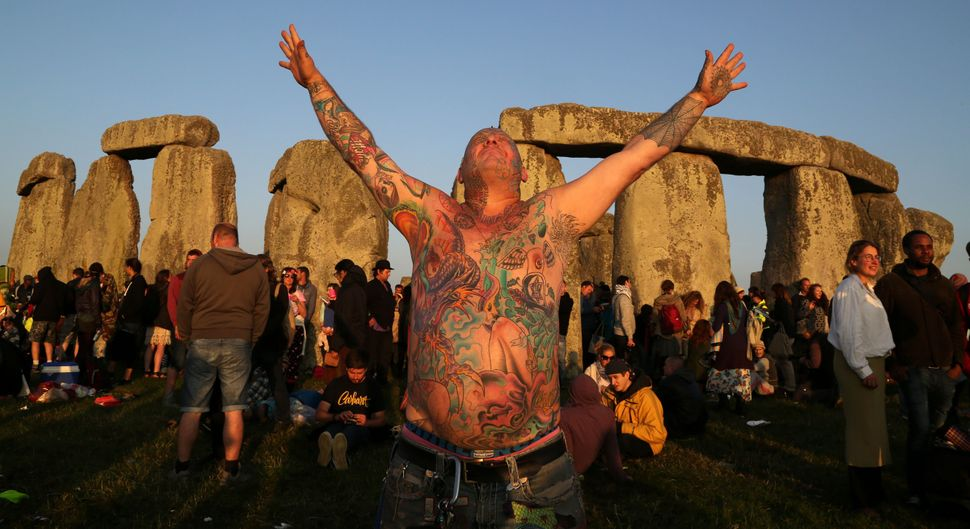 A reveler called Mad Alan (real name) celebrates as the sun rises at the prehistoric monument Stonehenge, near Amesbury in So