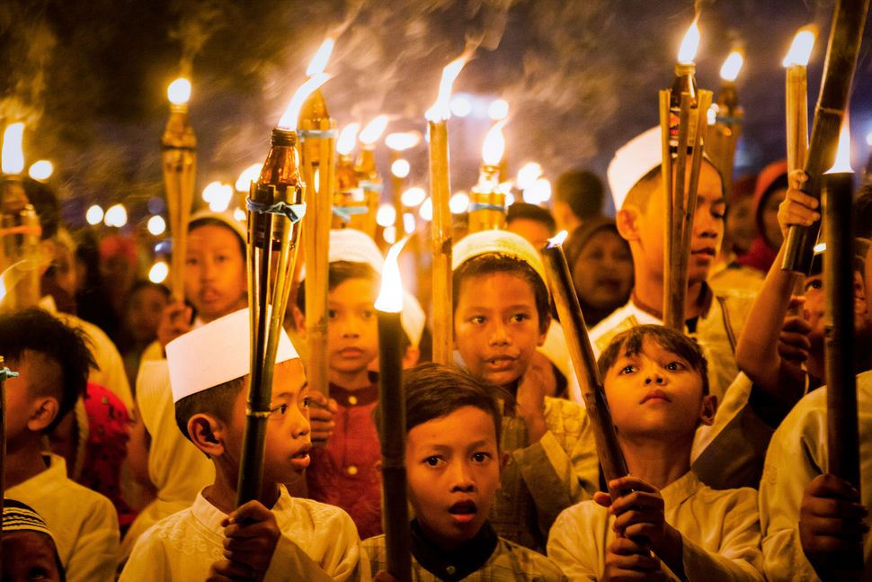 Children carry torches during a procession to celebrate the beginning of the holy month of Ramadan on June 27, 2014 in Jakar