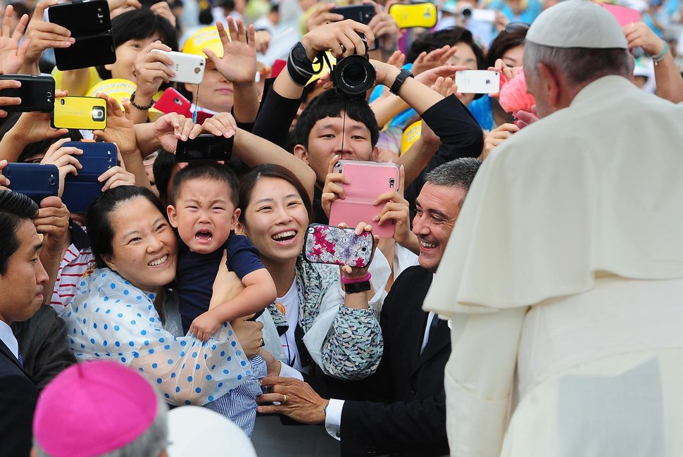 In this handout image provided by the Committee for the 2014 Papal Visit to Korea, The faithful greet Pope Francis upon his a