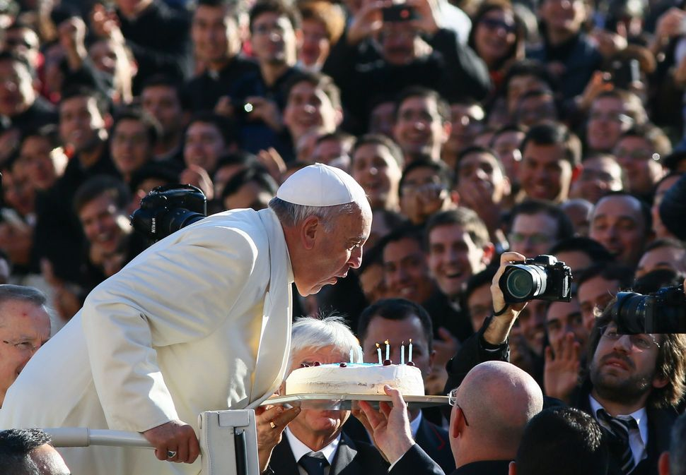 VATICAN CITY, VATICAN - DECEMBER 17: Pope Francis blows out the candles on his birthday cake during his general audience at S