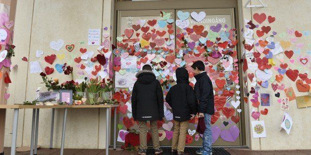 Boys read messages put up on the entrance to a mosque in Uppsala by neighbors pledging their support on January 2, 2015. The