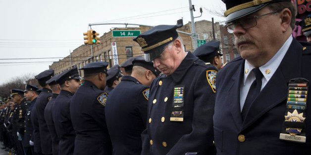 Some police officers turn their backs as Mayor Bill de Blasio speaks during the funeral of New York Police Department Officer