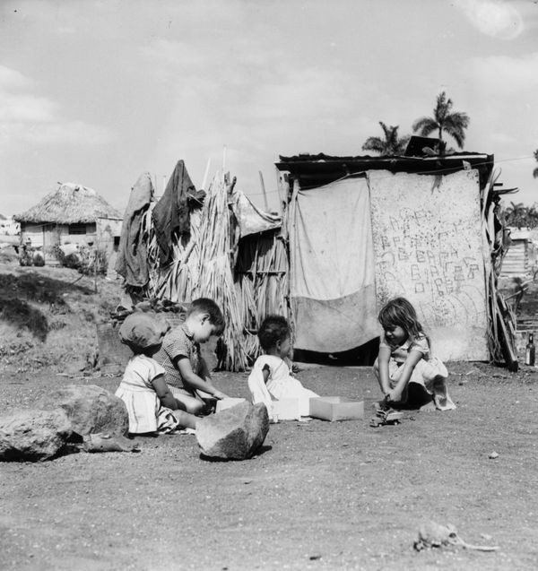 Circa 1950 - Children play outside their shanty homes in Oriente Province, Cuba.