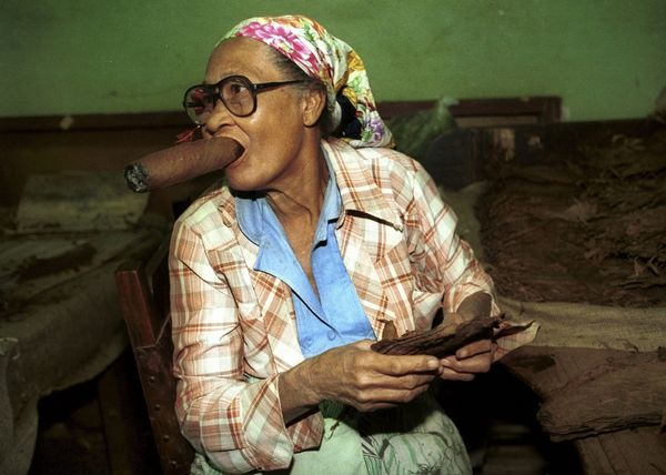 Date unknown - An old woman smokes an oversize cigar while working cigar maker Partagas in the Cuban capital Havana.