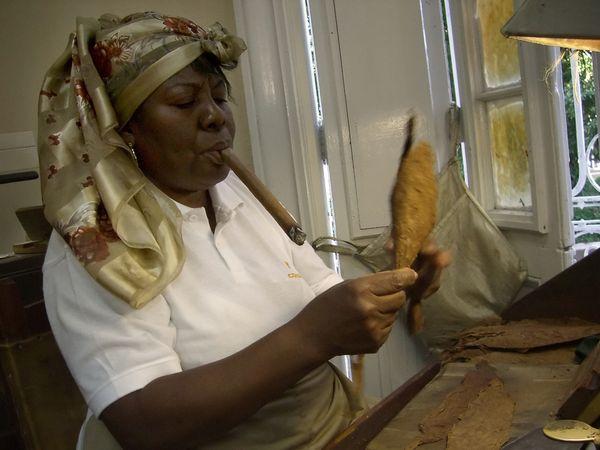 2006 - A cigar roller smokes a cigar while she prepares tobacco leaves at Cuban cigar manufacturer Cohiba's factory.