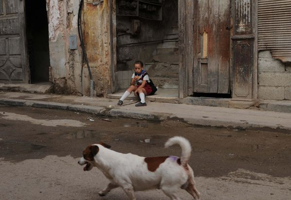 2009 - A Cuban schoolgirl sits at the foot of the entrance stairways in Havana.