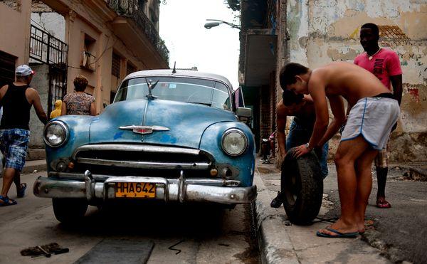 2012 - Men change the tire on an old Chevrolet in Havana.