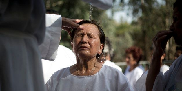 A Christian worshipper from Peru is baptized by a priest in the Jordan River, in Yardenit, northern Israel near the Sea of Ga