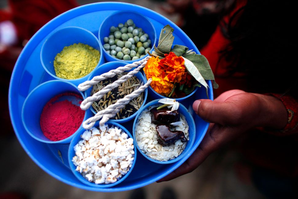 A Nepalese woman holds a plate containing a variety of items for performing a ritual during the first day of month long Swast