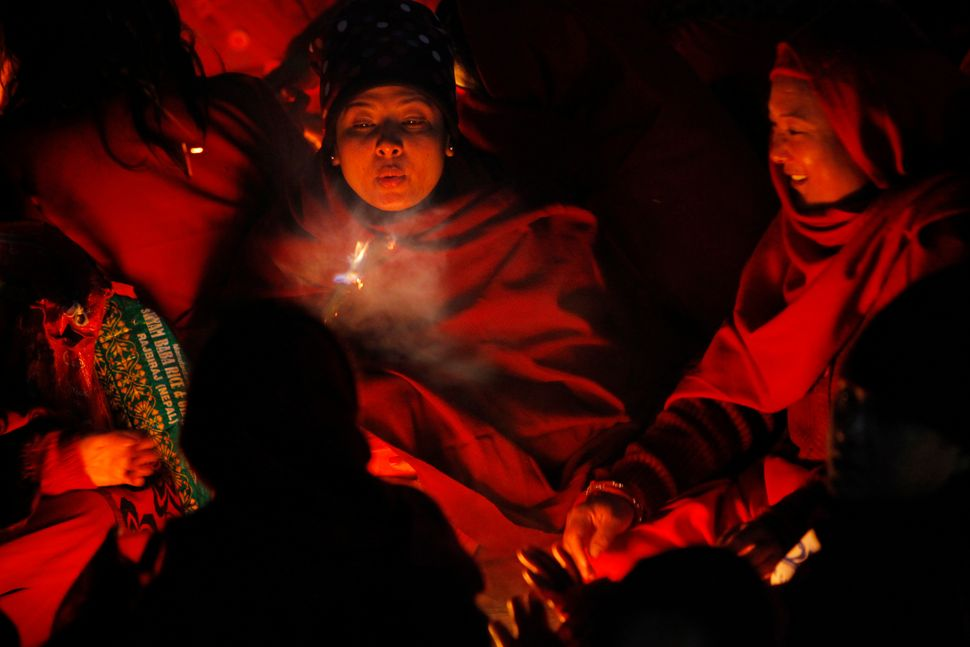 Nepalese women devotees sit around a bonfire  to warm themselves before they take holy deep in Salinadi River during the firs