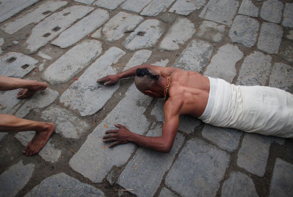Nepalese Hindu devotees prostrate on the ground to pray outside a temple as a part of a ritual during the first day of month
