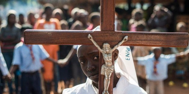 A girl carrying a cross arrives to celebrate mass at Saint Charles Lwanga church in Bangui on December 15, 2013. The Central