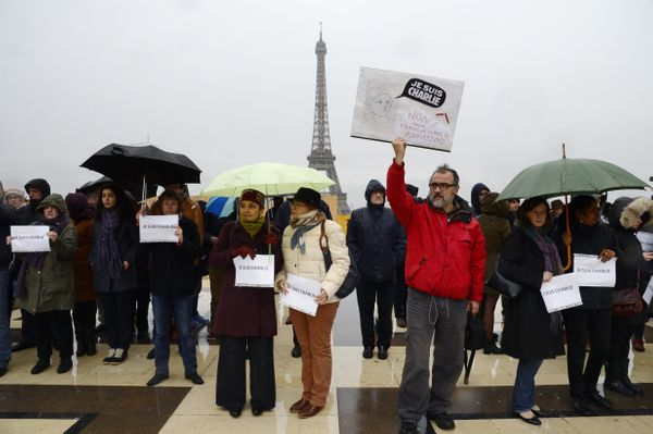 A man holds a sign reading 'Je suis Charlie' (I am Charlie) as people observe a minute of silence in front of the Eiffel Towe