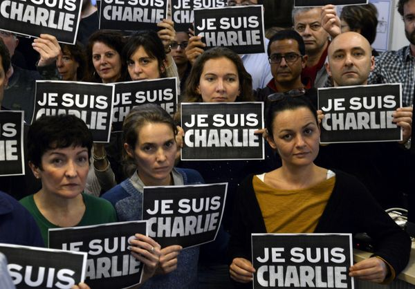 Journalists hold placard reading 'I am Charlie' as they hold a minute of silence, on January 7, 2015 at the redaction of Fren