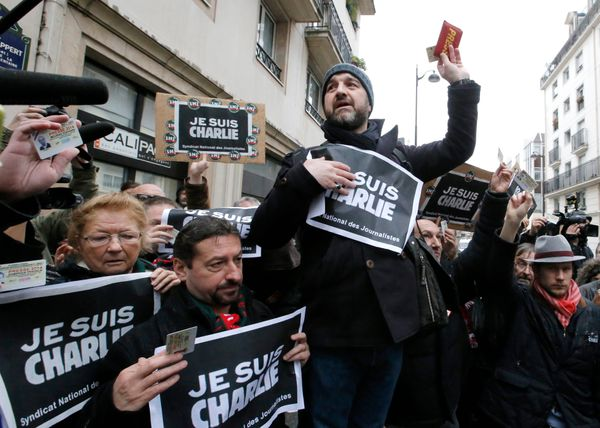 Journalist show their press cards during a minute of silence outside the Charlie Hebdo newspaper in Paris, Thursday, Jan.8, 2