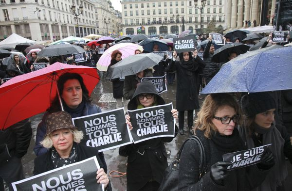 People hold signs reading 'Je suis Charlie' (I am Charlie) place de la Bourse in Paris as they observe a minute of silence on