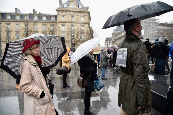 PARIS, FRANCE - JANUARY 08:  People wear the phrase 'Je Suis Charlie' (I am Charlie) as they take cover under umbrellas in th