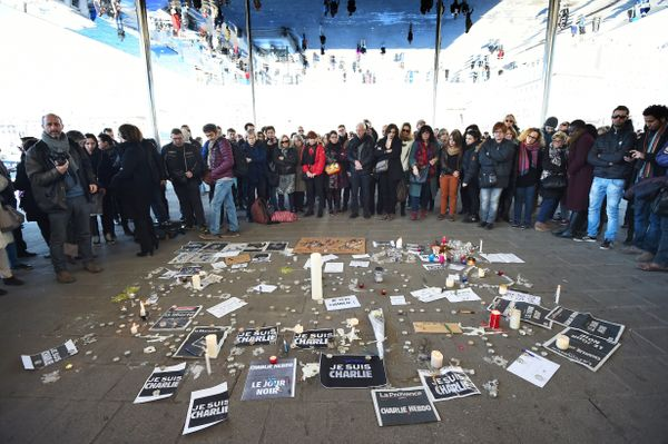 People gather next to signs reading ''I am Charlie'' and candles placed on the ground, after observing a minute of silence in