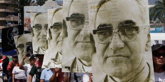 People march carrying portraits of slain Archbishop Oscar Arnulfo Romero on the 31st anniversary of his death in San Salvador