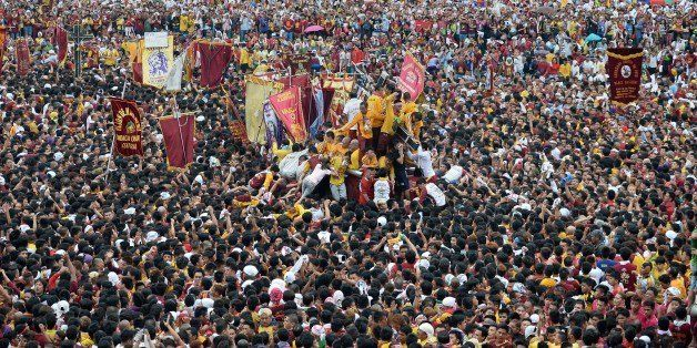 Thousands of devotees try to touch the religious icon of the Black Nazarene during the annual religious procession in Manila