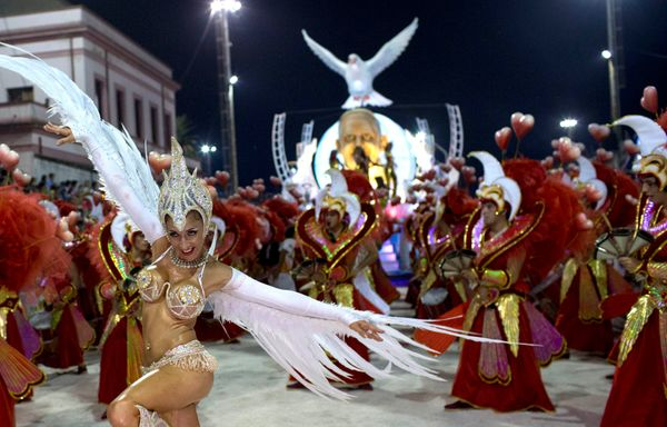 A dancer from the Ara Yevi samba school performs wearing white wings during a carnival parade of dancers and a float decorate