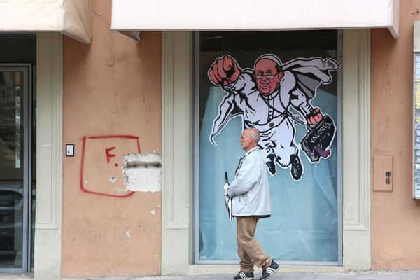 A man walks past the 'Super Pope Francis' graffiti in a street of L'Aquila five years after the earthquake on March 22, 2014